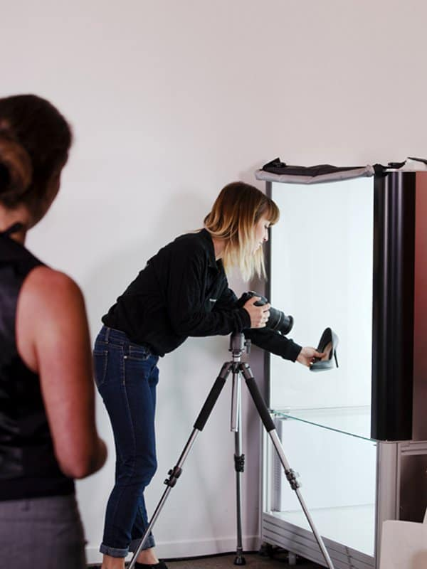 a girl is about to shoot a shoes into a photobox